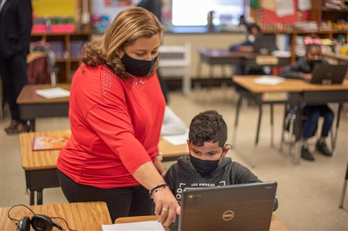 Teacher helping with Chromebook