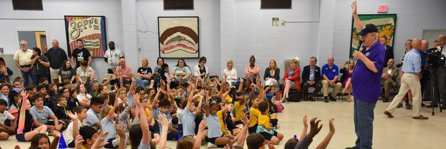 kids and adult raising their hands at a school
