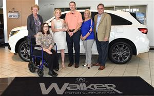 superintendent presenting award to walker acura